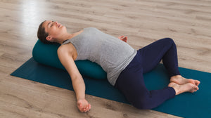Lady practicing lying down supta baddha konasana yoga pose