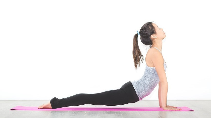 Young woman performing upward facing dog yoga pose