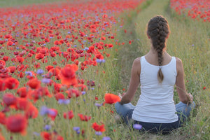 Lady practicing yoga in a poppy field