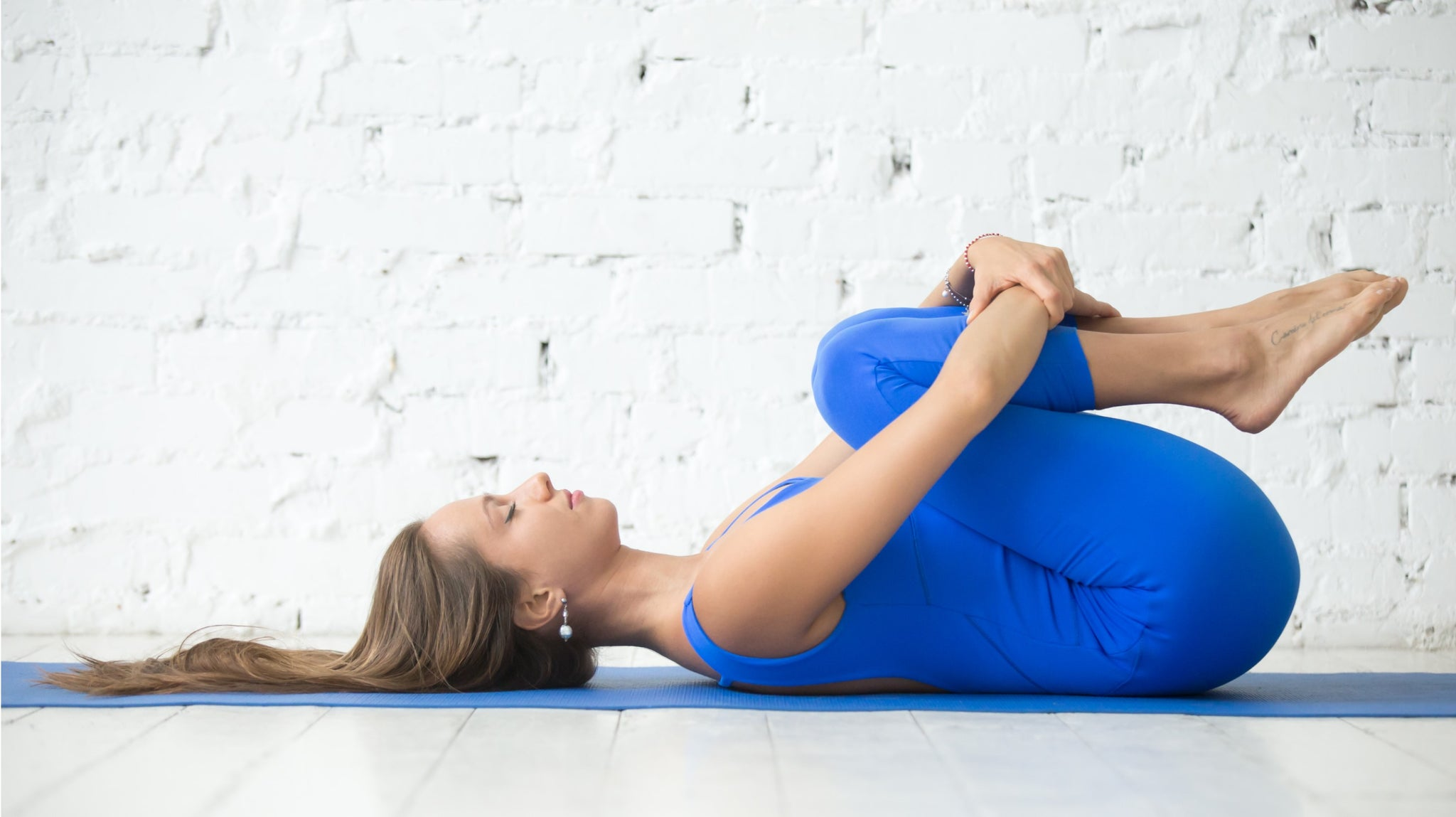 Young Woman performing the yoga posture wind relieving pose or apanasana