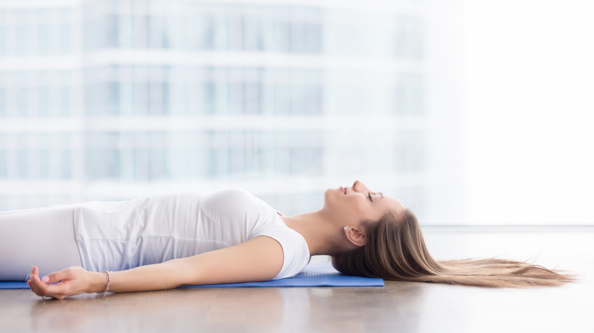 young woman practicing the yoga posture savasana