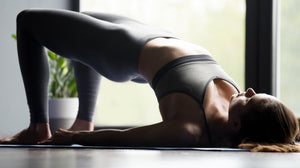 young woman practicing setu bandhasana - half bridge yoga pose