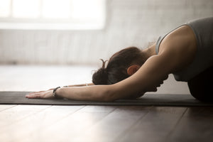 Young woman performing extended child yoga pose