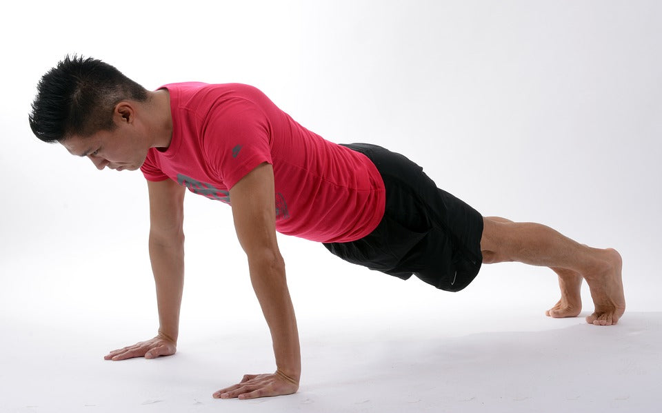 Middle aged man performing plank yoga pose.