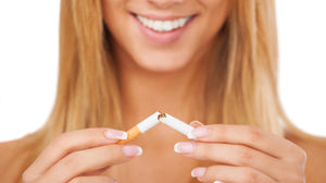 Young Woman tearing cigarette in half