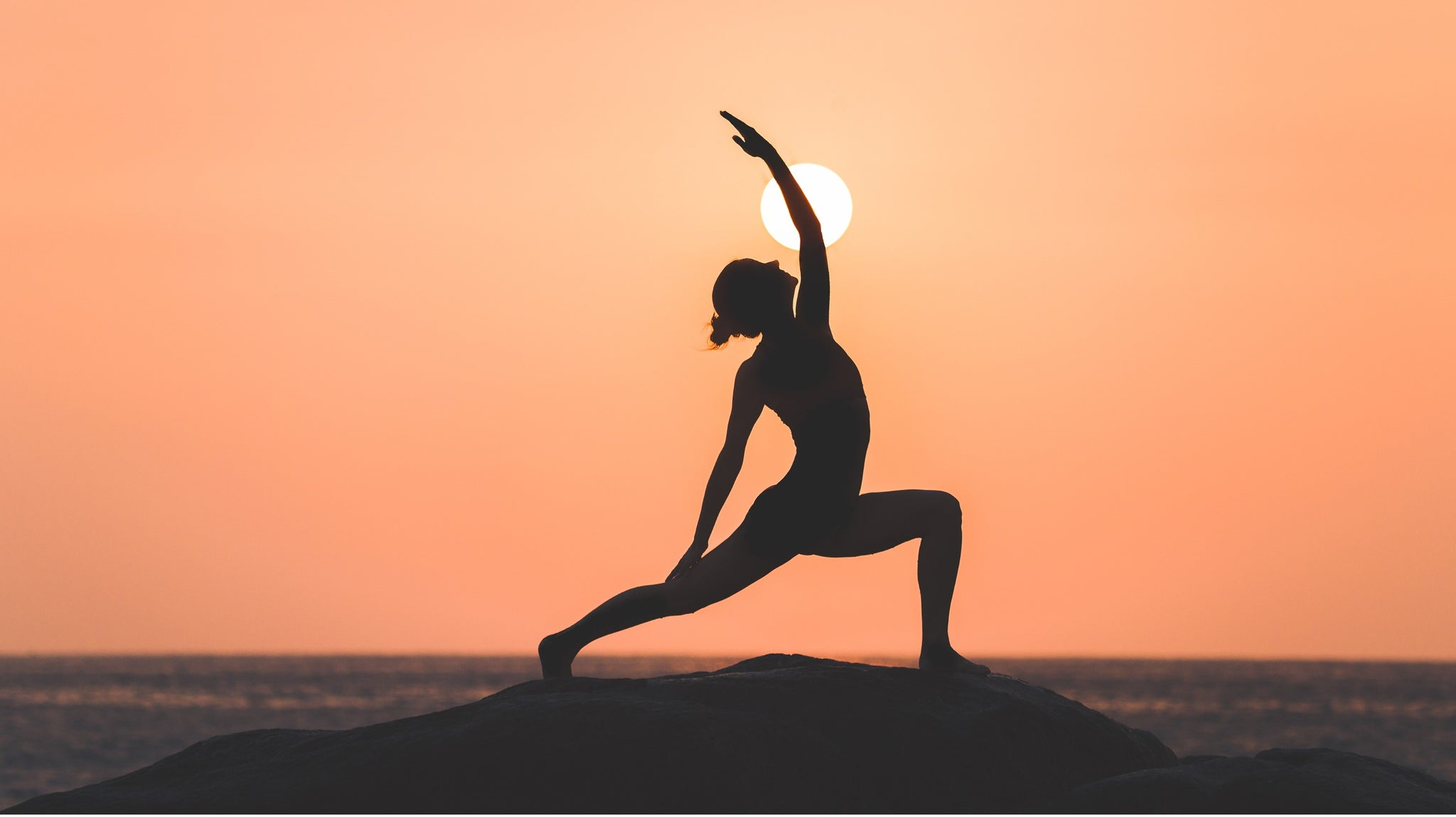 Woman practicing the yoga posture surya virabhadrasana - sun warrior