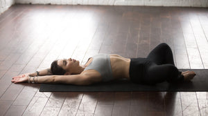 Lady practicing the yoga posture supta baddha konasana - lying down bound angle pose