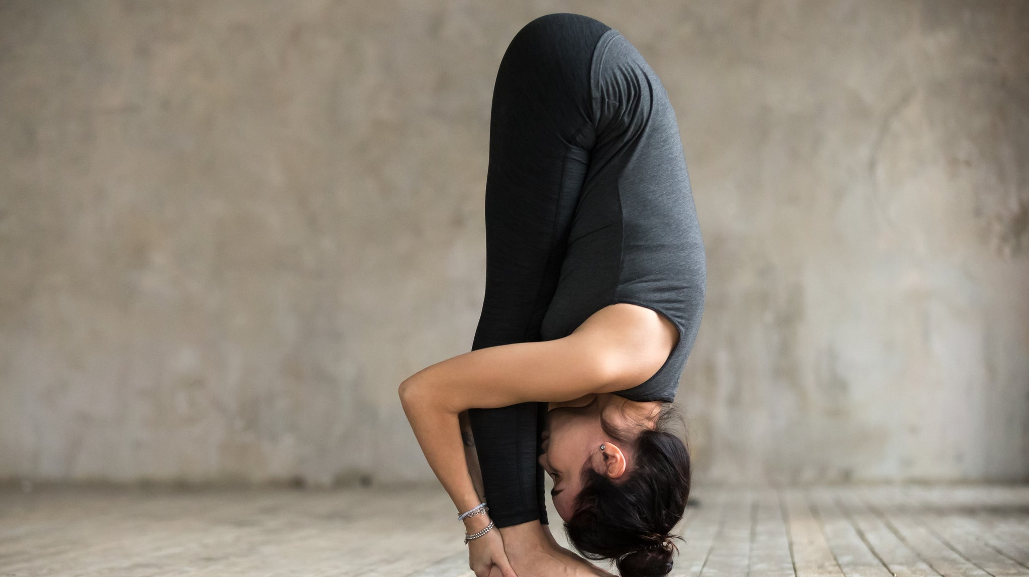 Attractive woman performing Uttanasana standing forward bend yoga pose.