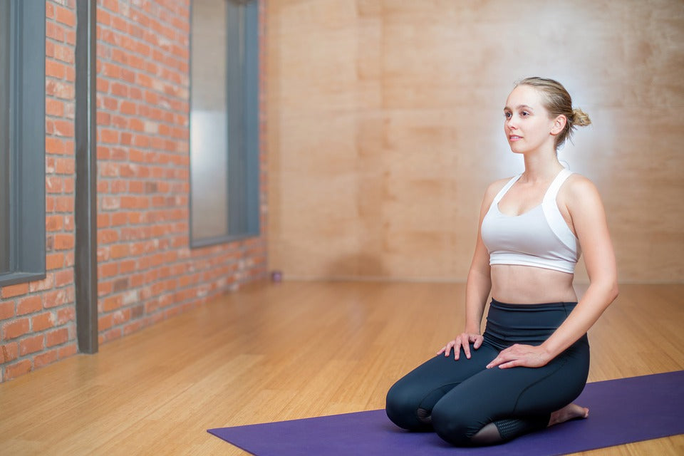 Woman practicing Vajrasana hero pose in a yoga studio