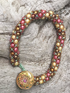 "Netted Treasure style beaded bracelet with Swarovski Glass Pearls in Rose, Cream, and Matte Bronze, with Sage and Rootbeer seed beads holding the netting together. A subtly iridescent Czech Glass button closure with beaded loop finishes this work of art. This bracelet measures 8 1/4""."