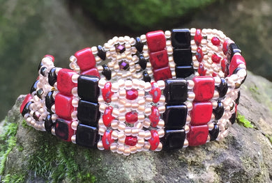 This lovely and intricately beaded Brocade bracelet of Red, Black and matte gold measures approximately 6 1/4