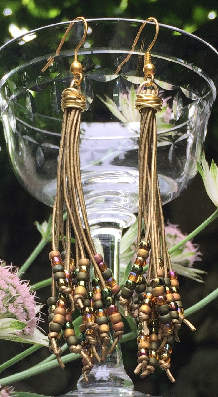 Sleek and slinky with Bronzed leather cords and seed beads in olive, mauve, dark bronze, iridescent topaz and matte gold, these cattail earrings generally measure 3 1/2 inches in length.