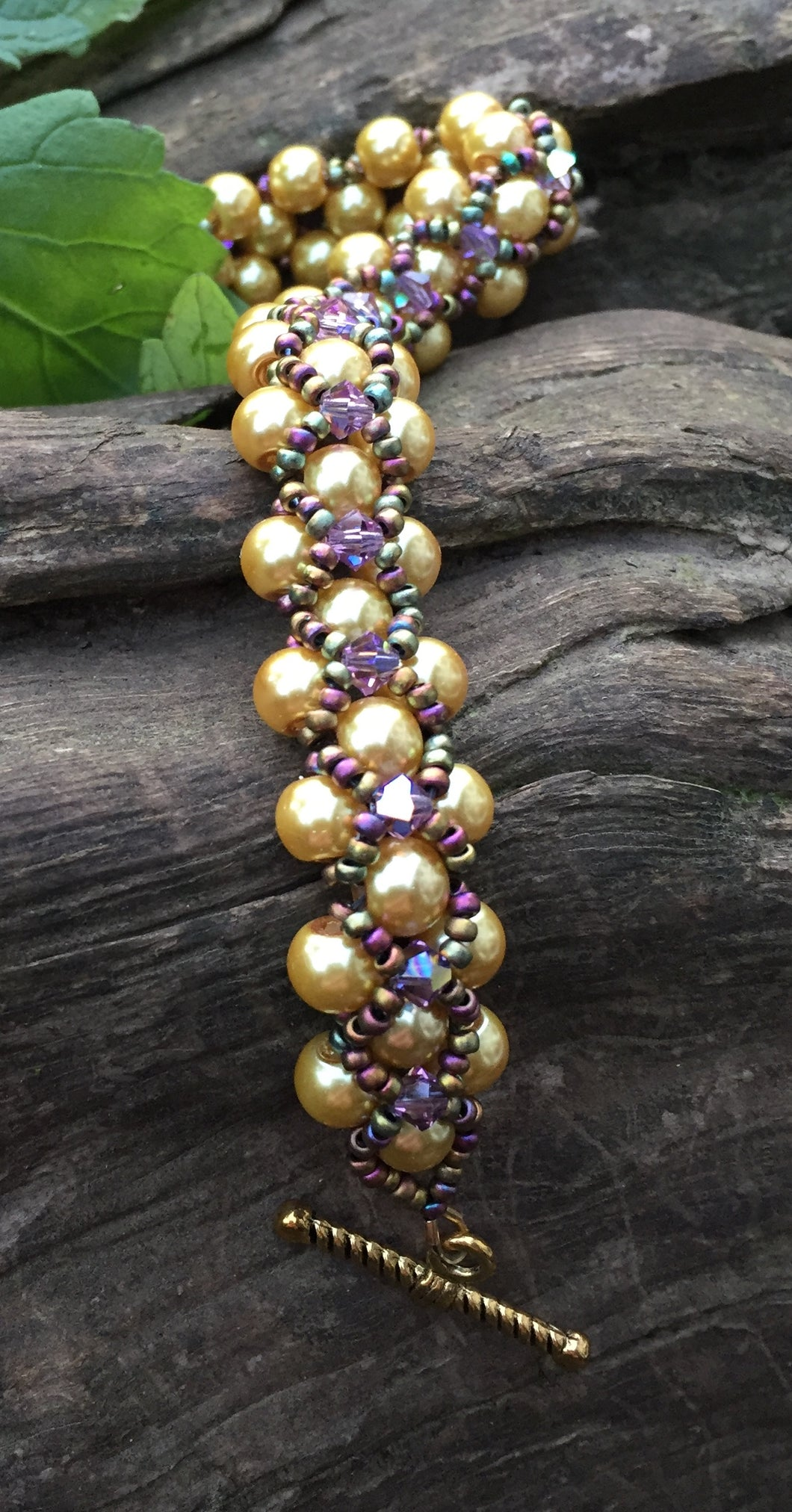 This Golden glass pearl and Amethyst bicone Swarovski crystal bracelet is netted together with Matte Iris seed beads and measures 7 7/8