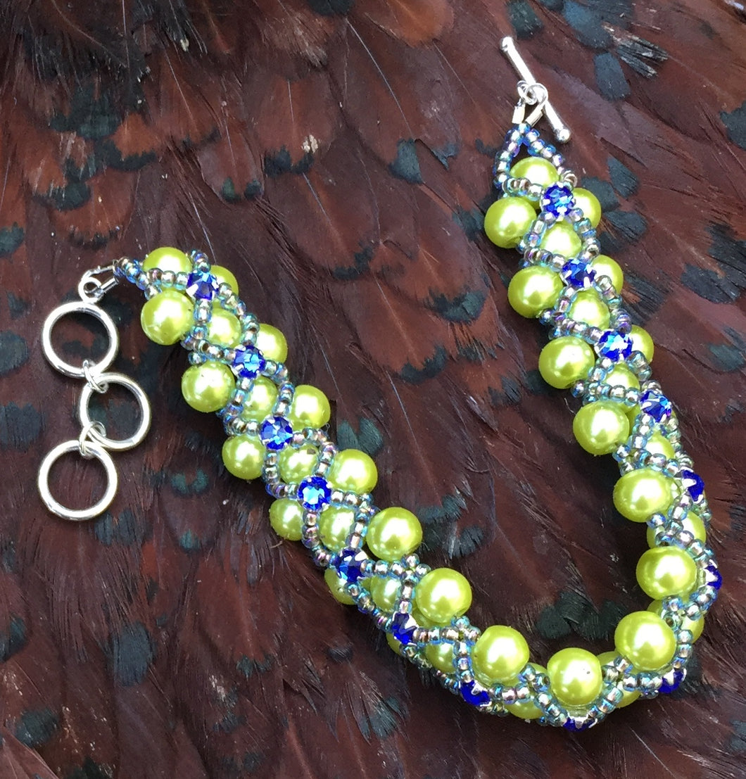 Lime green colored glass pearls and Sapphire Swarovski Montees are netted together with seed beads for this versatile bracelet. The bracelet is adjustable and measures between 7
