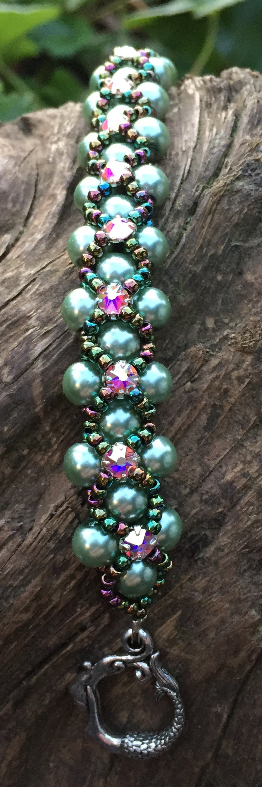This Sage colored pearl bracelet is entwined with Metallic Iris Seed beads and Swarovski Crystal Montees and measures 7 1/2