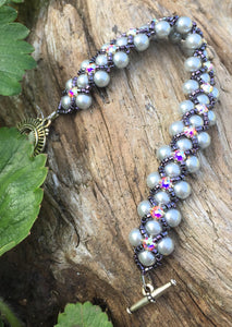 "This Silver glass pearl and Dark Purple Delica Seed Bead bracelet is topped with Swarovki Crystal Montees and measures 7 1/4""."