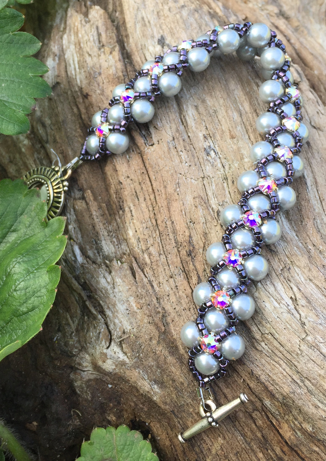 This Silver glass pearl and Dark Purple Delica Seed Bead bracelet is topped with Swarovki Crystal Montees and measures 7 1/4