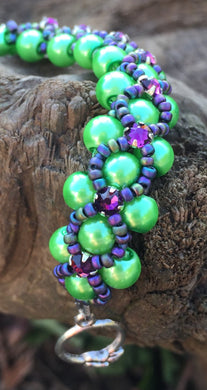 This Vivid Green glass pearl and Matte Iris seed bead bracelet is topped with Swarovski Purple Velvet Crystal Montees, and measures 7 1/2