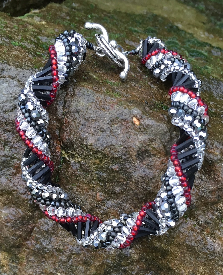 This meticulously woven Helix Spiral Bracelet includes Czech fire-polished glass beads in Crystal, Red, Black and Metallic gray.   8 1/4