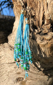 "Breezy and dangling light blue leather cords with green silver and light blue seed beads, these Cattail Style Leather Earrings measure approximately 3 3/4""."