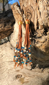 "Free flowing medium brown leather cords with deep blue, cream, brown and gold seed beads, these Cattail Style Leather Earrings measure approximately 3 1/2""."