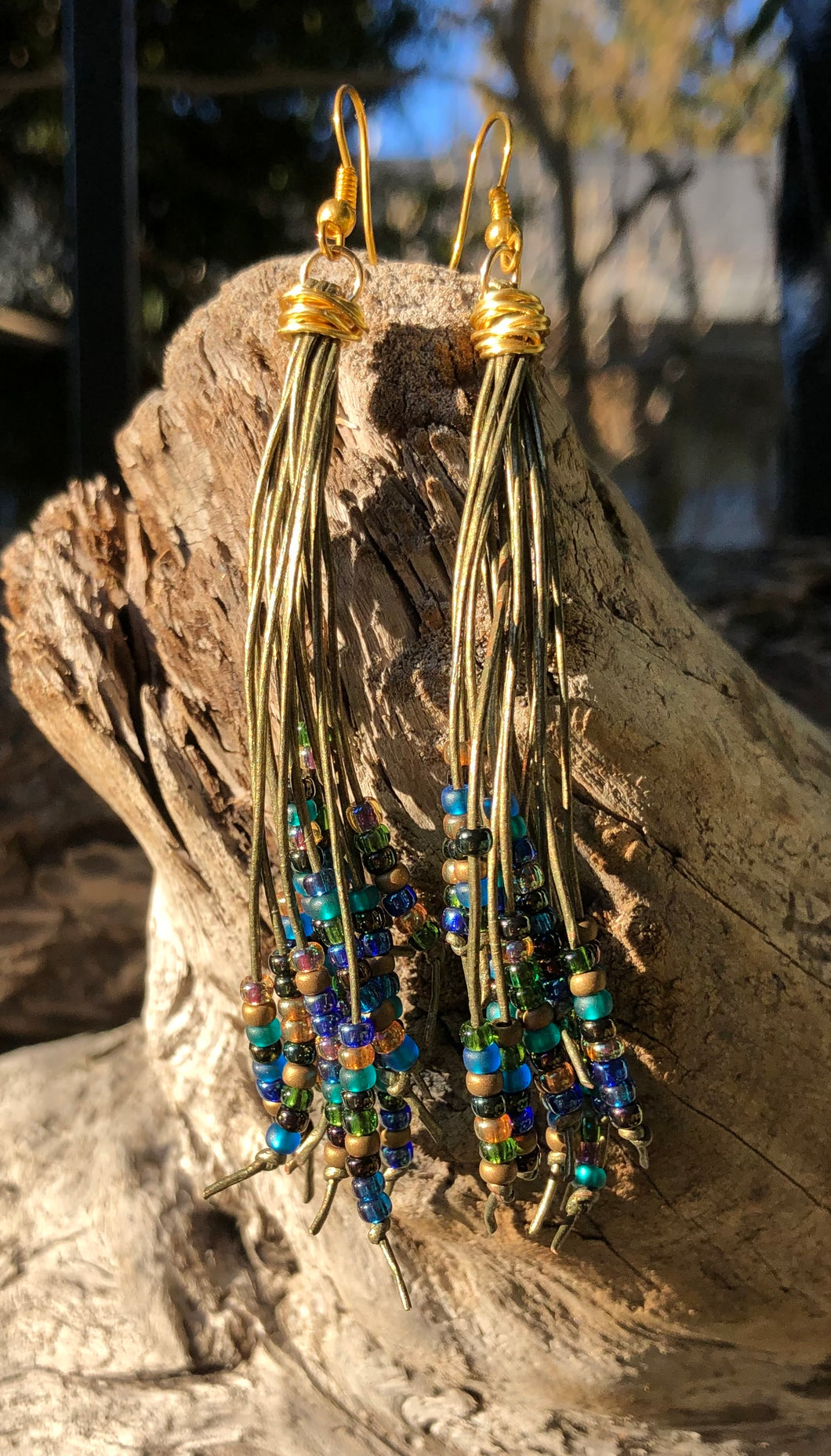 These Cattail Style Leather Earrings on Bronze Leather with seed beads in bronze, teal, green, amber, blue and purple measure approximately 4
