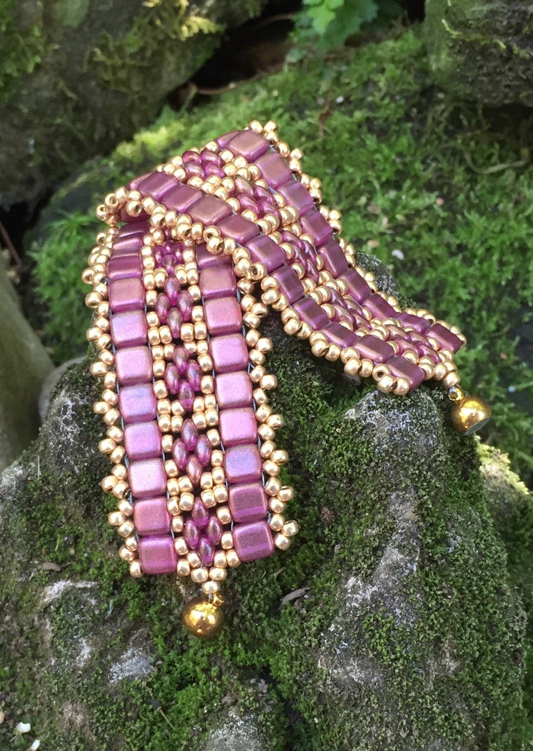 This bead woven bracelet combines gold toned Pink Czech Glass tiles with Pink and Gold glass beads and measures 6 3/4