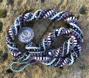 "This meticulously woven helix necklace consists of Czech Glass beads in purple, black, green and cream and it ends with an iridescent Czech glass button clasp.  It is adjustable and can be worn between 15"" to 16 1/2""."