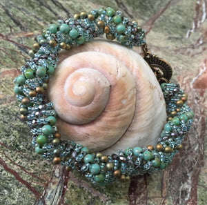 "Dutch Spiral beaded bracelet pattern using Czech Fire-polished glass, Czech druks, and seed beads in Turquuoise Green, pale clear blue and Bronze. This bracelet measures between 8 1/4"" and 8 1/2"""