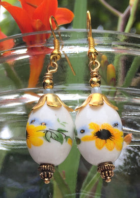 These handpainted oval ceramic earrings have Blackeyed Susans and tiny light blue violets and measure 1 1/2