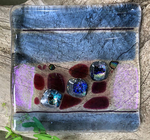 "This transparent and Dichroic fused glass dish has the charm of both stripes and speckles! While flat in design, the surface is bubbly, making it a great option for holding jewelry or incense. This dish measures almost 4"" x 4""."