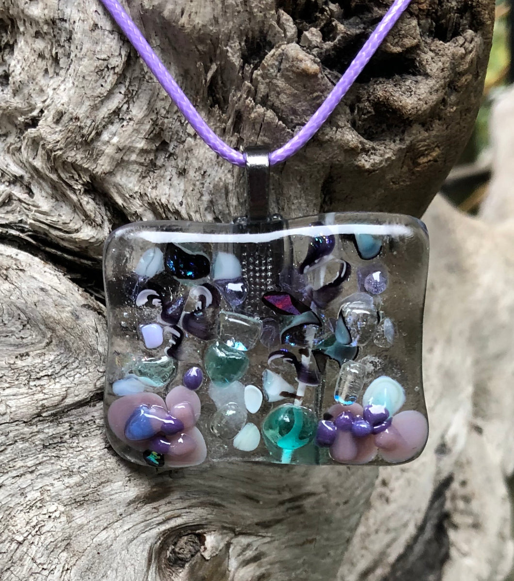 "This Fused Glass Butterfly Pendant is all aflutter with dichroic glass, Murrini, and other garden colored bits! It measures 1 1/2"" by 1 5/8"", and rests on a lavender waxed Irish cotton cord which is adjustable from 17 1/2"" to 19 1/2""."