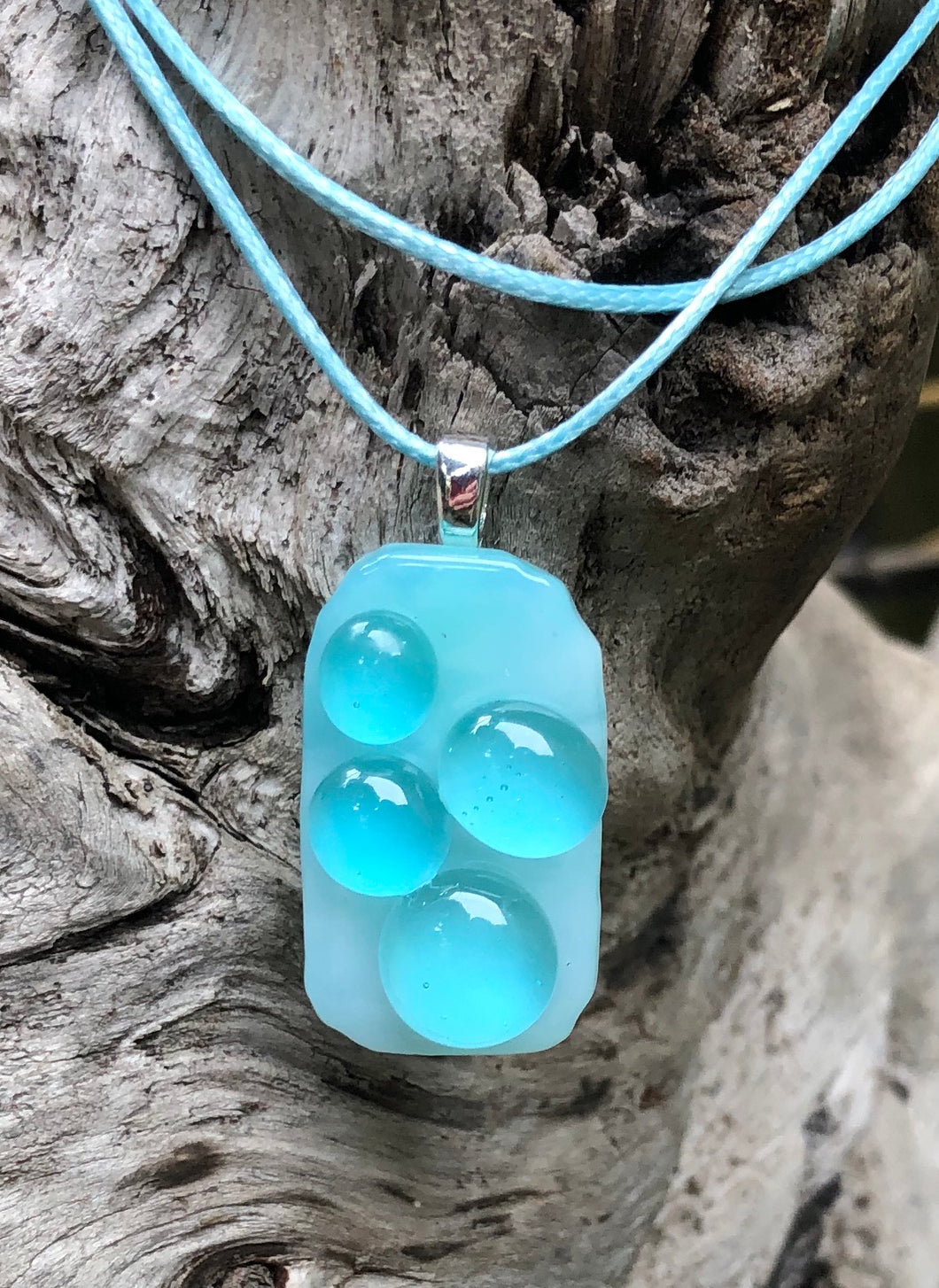 "The Bubblicious Aqua Bubbles Fused Glass Pendant measures approximately 1 1/2"" x 3/4"" on floats on a waxed Irish cotton cord which is adjustable from 17 1/2"" to 19 1/4""."