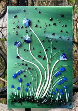 "Sultry Creamy White Vitrigraph stems topped with serene torch work Bluebells begin to emerge in your garden for an early Spring! The background flaunts distant purple blooms. This little garden fused glass art panel scene measures 5"" x 8""."