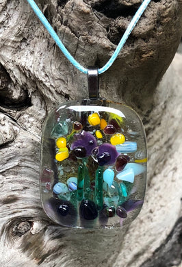 "So much activity on this fused glass pendant, could be pollinators, butterflies, birds... this pendant with Purples, Aquas, Yellows and Greens measures 1 5/8"" by 1 3/8"". The light blue waxed Irish cotton cord is adjustable from 17 3/4"" to 19 3/4""."