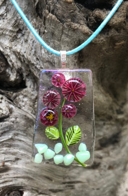 "Lovely burgundy blooms in an aqua rock garden on an iridescent base! This pendant measures 1 3/8"" by 1"". The pale aqua waxed Irish cotton cord is adjustable from 17 1/2"" to 19 1/4""."
