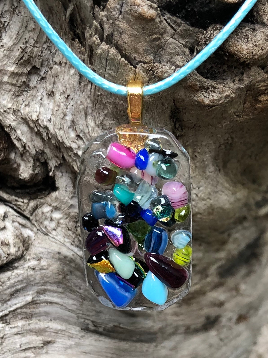 "This colorful fused glass pendant of the Pixie Dust Collection is 1 1/4"" by 3/4"" and the light blue waxed Irish cotton cord is adjustable from 18"" to 19 3/4"". Elements include dichroic glass!"