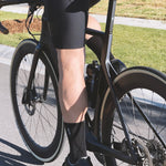 Male cyclist on bike wearing Relm cycling socks in black