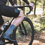 Man sitting on Canyon bike wearing Relm Cycling black bib shorts and classic grey socks