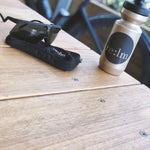 Black cycling pocket pouch, gold bidon and Alba Optics sunglasses on table.