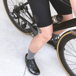 Woman sitting on bike wearing Relm Cycling bib shorts in black and Lake Cycling shoes