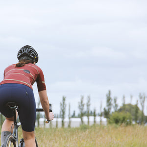 Woman riding bike wearing Relm Cycling navy bib shorts, evolve jersey in offset design and Lazer helmet