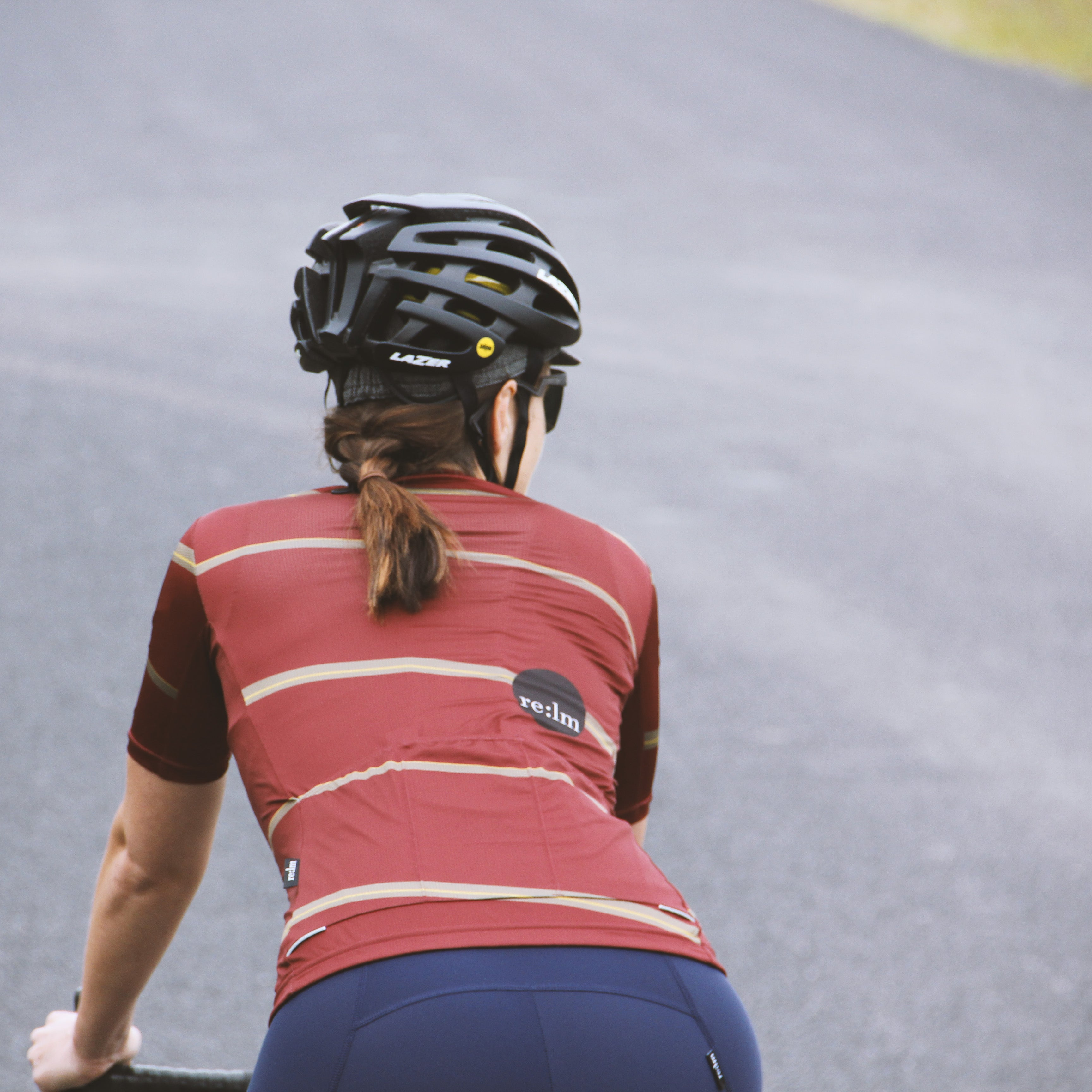 Woman riding bike wearing Relm Cycling jersey in offset design and Lazer helmet