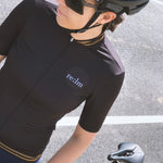 Woman wearing Relm Cycling jersey in varsity design and Alba Optics sunglasses