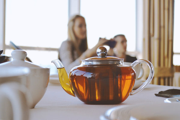 Glass teapot with people in the background