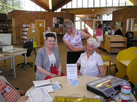 A volunteer helping clients at a hearing aid aftercare clinic.