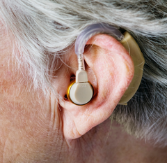 Photo of a hearing aid being worn in the ear of an old woman