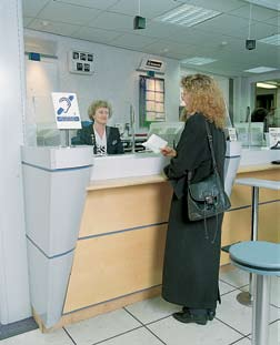 Woman speaking to someone at a counter with the Contact Under The Counter Loop system