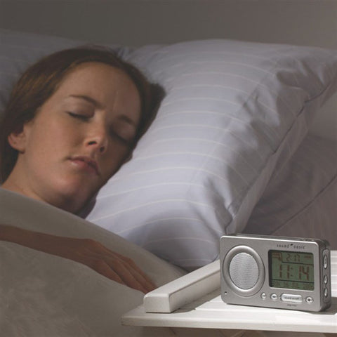 Woman asleep in bed with a Sound Oasis Travel Sound Therapy System on the bedside table