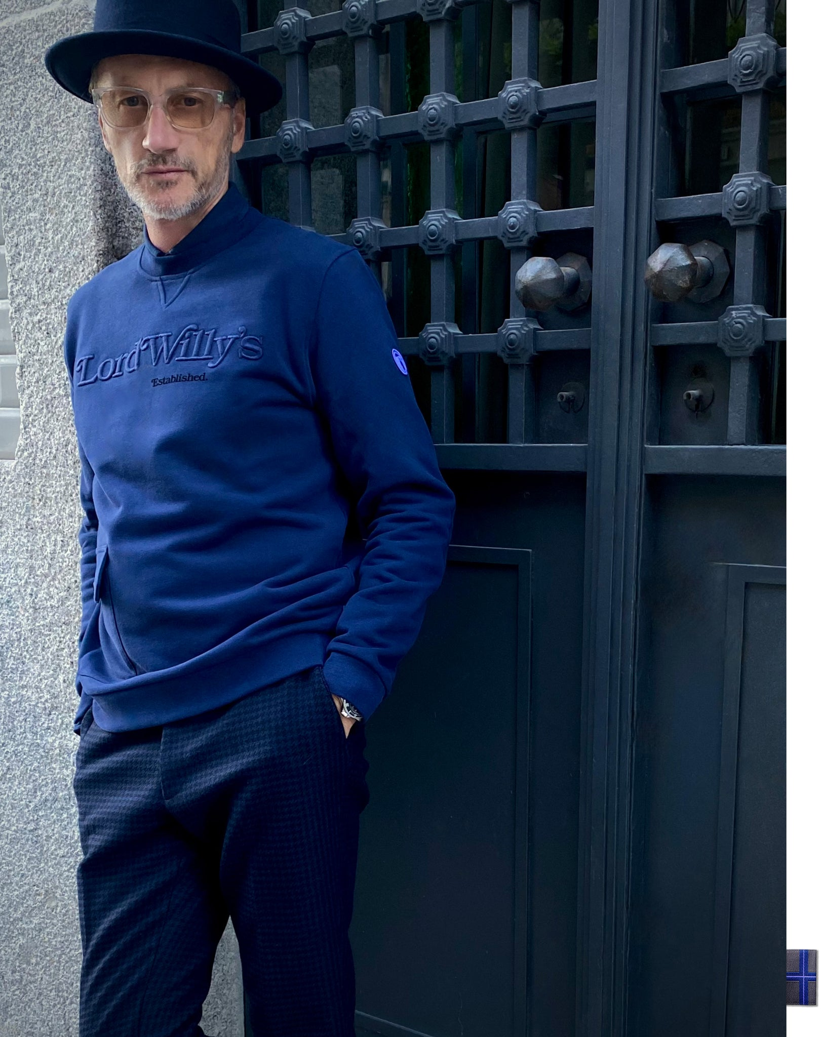 Man in navy sweatshirt with Lord Willy's embroidered on it.